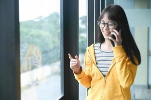 une étudiante asiatique a appelé son amie à la fenêtre.pour se préparer à l'examen d'entrée à l'université. photo