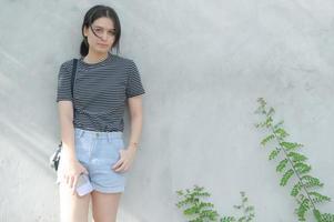une adolescente s'appuie contre un mur de ciment et regarde la caméra. photo