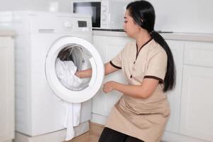 jeune et belle femme de chambre asiatique chargeant la machine à laver des vêtements blancs dans une chambre d'hôtel photo