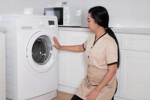 jeune et belle femme de chambre asiatique chargeant les vêtements de la machine à laver dans la chambre d'hôtel photo