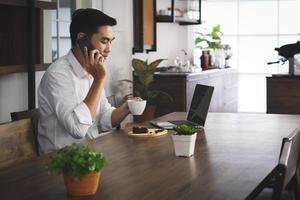 homme asiatique assis dans le café, buvant du café et du petit-déjeuner, se réveillant au loin. concept commercial et technologique photo