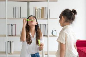 jeune mère asiatique plaing des bulles de savon avec son enfant dans le salon à la maison en été. concept de famille ensemble photo
