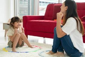 jeune enfant asiatique jouant au jeu avec sa mère dans le salon à la maison. concept de famille ensemble photo