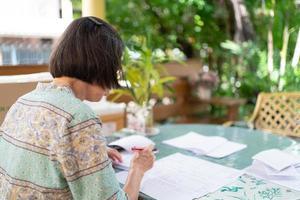 une femme asiatique âgée calcule le solde des revenus et des dépenses sur la terrasse de la maison photo