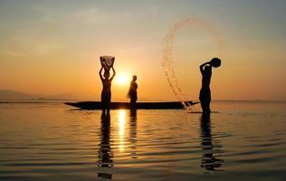 silhouette de pêcheur et de son fils debout dans le lac près d'un bateau et utilisant un pot pour éclabousser de l'eau photo