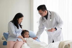 un médecin asiatique rend visite à une jeune fille et à une mère malade et admise au service pédiatrique de l'hôpital. concept de soins de santé et médical photo