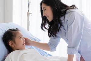 mère asiatique s'occupe de sa fille qui est malade, a de la fièvre et dans le service de pédiatrie de l'hôpital. concept de soins de santé et médical photo