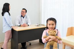jeune fille asiatique tenant un ours en peluche et debout devant sa mère et son médecin dans une clinique de développement hospitalier. concept de soins de santé et médical photo