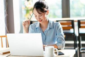 portrait de femme d'affaires asiatique travaillant dans un café photo
