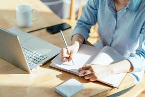 image de la main d'une femme prenant des notes et faisant des plans photo