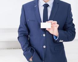 main de l'homme montrant la carte de visite - gros plan tourné au bureau, blanc, vue de dessus photo