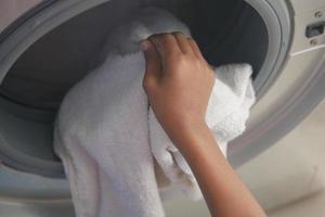 homme mettant la chemise dans la machine à laver. photo