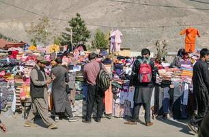 gilgit, pakistan, 2017 - personnes choisissant des marchandises dans un étal de vêtements local. photo