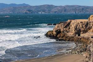 forte vague frappant la plage rocheuse de l'océan pacifique. photo