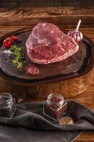 Croûte de bœuf cru picanha brésilien sur une planche à découper en résine de bois avec des épices. table en bois. photo