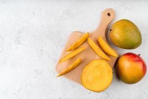fruits mando tranchés sur une planche à découper en bois vue de dessus sur fond de marbre photo
