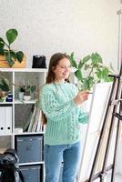 Jeune artiste adolescente tenant une palette de couleurs travaillant dans son studio photo
