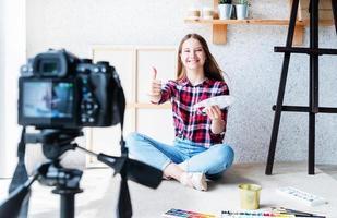 Jeune femme faisant une vidéo montrant le pouce pour son blog sur l'art à l'aide d'un appareil photo numérique monté sur trépied
