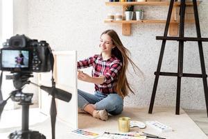 femme faisant une vidéo pour son blog sur l'art à l'aide d'un appareil photo numérique monté sur trépied