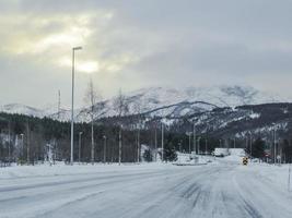 conduire à travers une route blanche enneigée et un paysage en norvège. photo