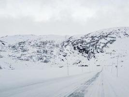 conduire à travers une route enneigée et un paysage en norvège. photo
