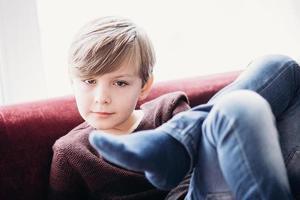 enfant mignon garçon assis sur un canapé, les jambes croisées photo