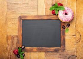 tableau noir avec beignet glacé rose photo
