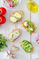 préparation de sandwichs d'été - pain, guacamole, ruccola, tomates, radis, concombre