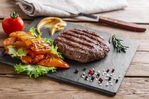 burger grill avec légumes et sauce sur une surface en bois