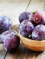 grosse prune violette avec des gouttes d'eau et des feuilles photo