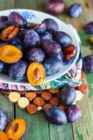 prunes juteuses fraîches sur une planche de bois photo