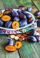 tranches de prune bleue juteuse sur une planche de bois photo