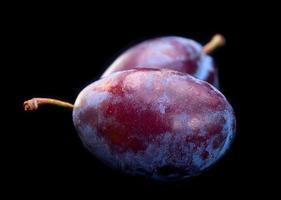 légume prune sur fond noir photo
