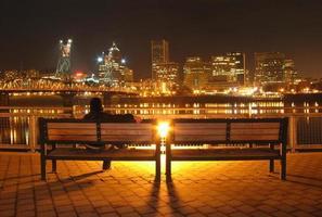 personne assise sur un banc avec vue sur le centre-ville photo