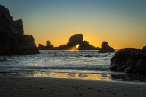 rayonnant à travers un rocher au coucher du soleil