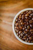 grains de café en tasse sur fond de bois grunge
