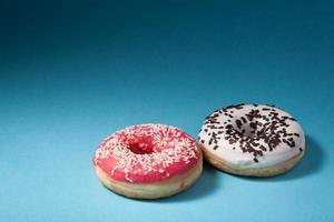deux beignets avec glaçage rouge et blanc isolé sur bleu