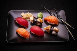 Sushi d'anguille, de saumon et de thon avec des baguettes