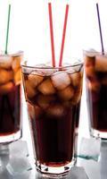 trois verres de cola avec de la glace et des pailles
