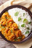 crevettes au curry avec du riz sur la plaque en gros plan. vue de dessus verticale photo
