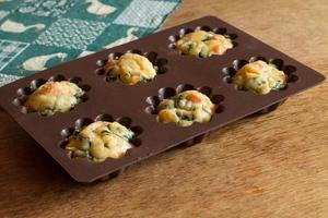 muffin au saumon, épinards et fromage dans des ustensiles de cuisson en silicone