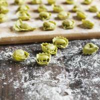 tortellini non cuits avec du fromage sur une table