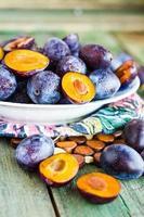 prunes bleues crues sur une assiette ronde, végétalienne photo