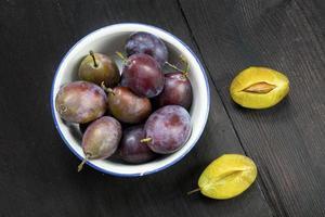 prunes dans un bol sur bois brun foncé photo