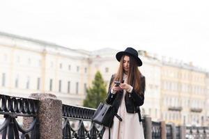 À la mode, un message de lecture féminin sur téléphone portable pendant la promenade à l'extérieur photo
