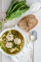 soupe à l'oseille avec boulettes de viande, pain, crème sure, serviette à carreaux photo