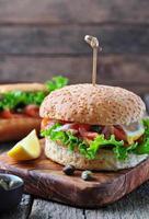 burger au saumon mariné, laitue, oignon blanc et câpres