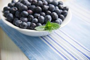 Assiette blanche ion bleuets frais sur la table de la cuisine photo