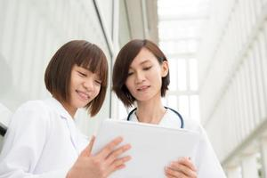 médecins asiatiques ayant une discussion avec tablette pc numérique