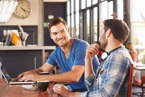deux jeunes hommes travaillant sur des ordinateurs dans un café